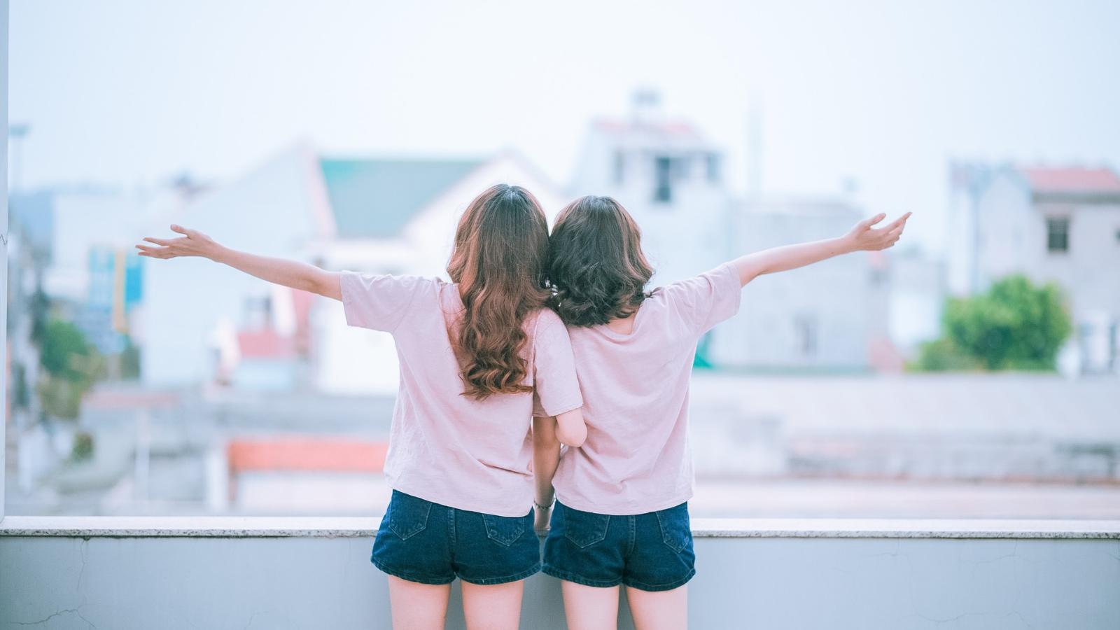 Zwei junge Frauen genießen die Aussicht vom Balkon.