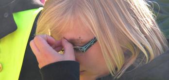 Junge Frau greift sich an den schmerzenden Kopf.